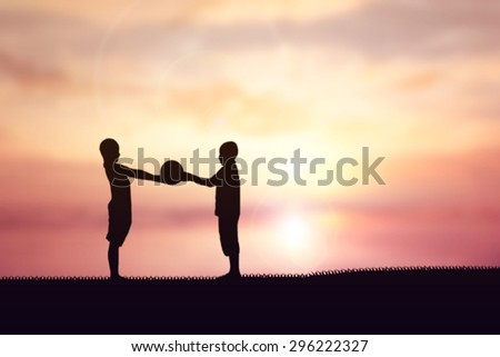 Silhouette of children playing soccer background sunset.