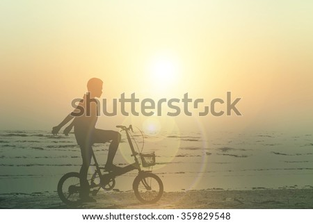 Silhouette of children riding bicycles on the beach. - stock photo