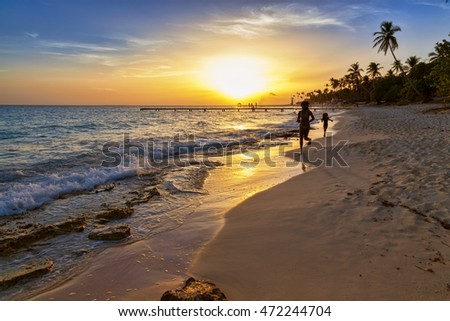 Silhouette of children running along the coastline. Caribbean sea beach sunset. Tropical beach in Caribbean sea, Dominican Republic. Couple are waiting sunset in Caribbean beach.
