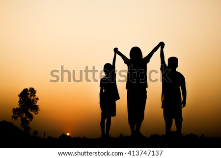 Silhouette of children with beautiful sunset background.