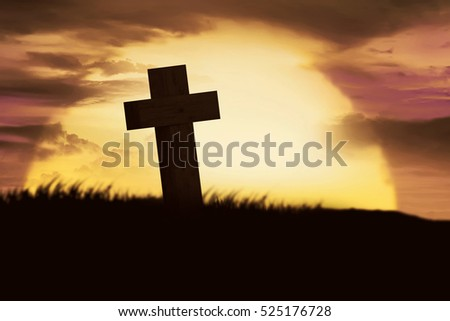 Silhouette of christian cross over sunset background
