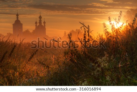 Silhouette of church in morning fog at sunrise - stock photo