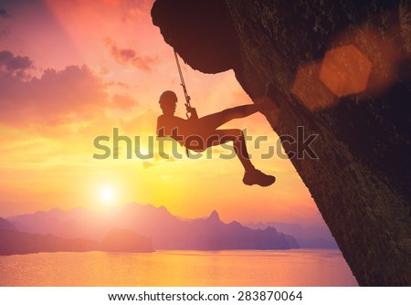 Silhouette of climber on a cliff against beautiful red sunset above the sea - stock photo