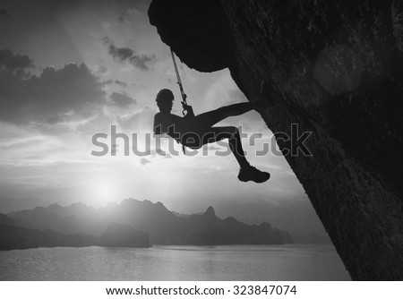 Silhouette of climber on a cliff against beautiful sunset above the sea. Black and white - stock photo