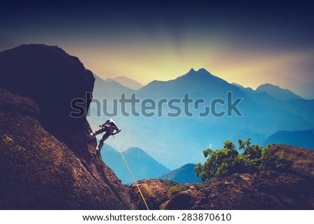 Silhouette of climber on a cliff against beautiful sunset in a high mountains - stock photo