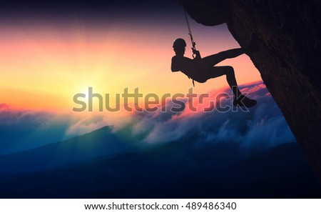 Silhouette of climber on a cliff against sunset in a mountain valley