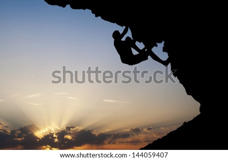 silhouette of climber on overhanging rock