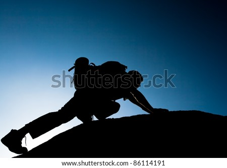 Silhouette of climbing young adult at the top of summit with aerial view of the blue sky - stock photo