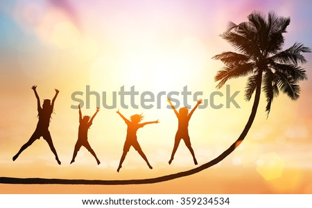 silhouette of coconut tree and people jump on sunset beach