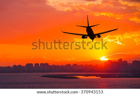 silhouette of commercial plane flying over a city during sunrise