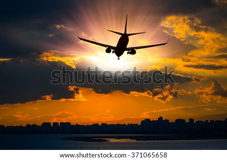 silhouette of commercial plane flying over a city during sunrise - stock photo