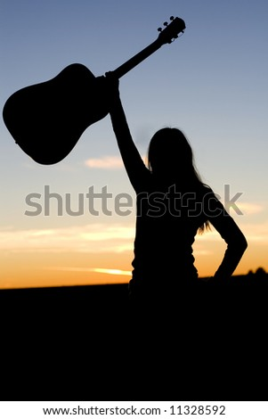 Silhouette of confident woman holding her guitar in the air. - stock photo
