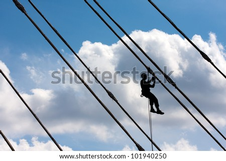 Silhouette of construction climber against blue sky - stock photo