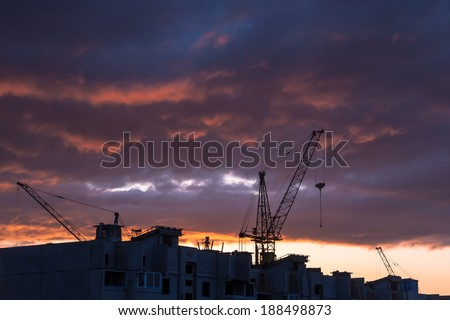 Silhouette of construction crane on dramatic sky background at the sundown