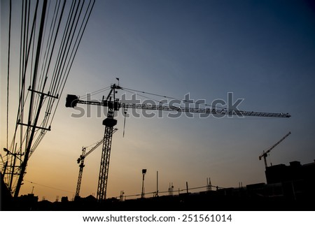 Silhouette of construction crane with sunset sky - stock photo
