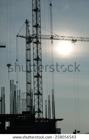 Silhouette of construction cranes on background sun