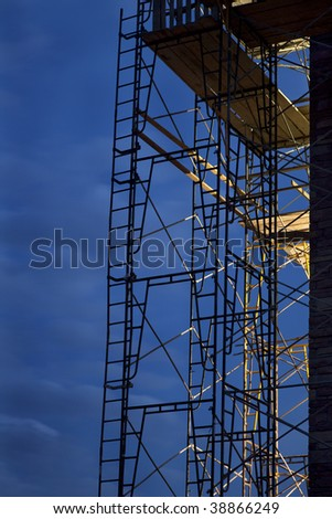 silhouette of construction scaffolding against nighttime sky with a strong light coming from building interior
