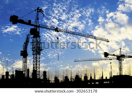 silhouette of construction site crane with blue sky - stock photo