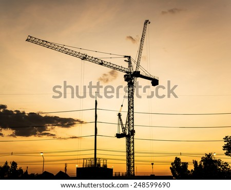 Silhouette of construction site in sunset. - stock photo