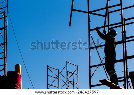 silhouette of construction worker against sky on scaffolding with ladder on building site