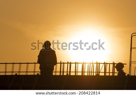 Silhouette of construction worker during sunset - stock photo