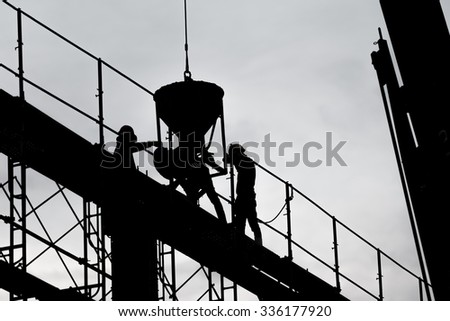 Silhouette of construction worker on scaffolding in the construction site. - stock photo