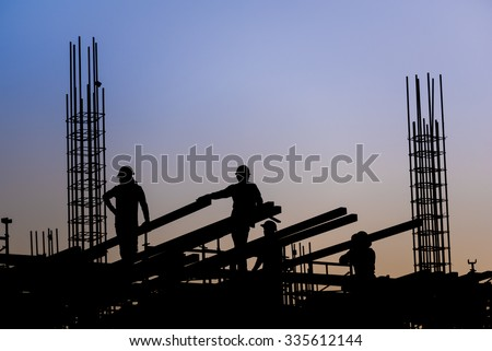 Silhouette of construction worker on scaffolding in the construction site before to night time.