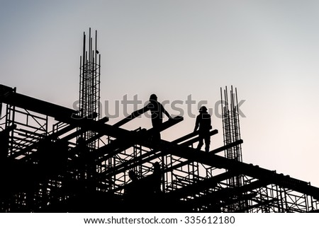 Silhouette of construction worker on scaffolding in the construction site before to night time. - stock photo