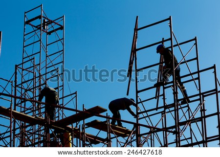 silhouette of construction workers against sky on scaffolding with ladder on building site - stock photo