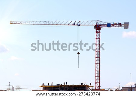 silhouette of construction workers and red crane on construction site at sunrise - stock photo