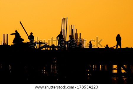 Silhouette of Construction Workers at Sunset - stock photo