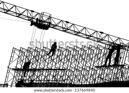 Silhouette of construction workers on metal scaffolding  - stock photo