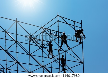 Silhouette of construction workers on scaffold working under a blue sky - stock photo