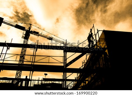 Silhouette of construction workers on scaffold working under a hot sun - stock photo