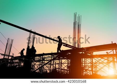 Silhouette of construction workers working on scaffolding at a high level by the standards set must include a safety belt for safety. Heavy industry And Safety at Work concept. - stock photo