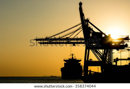 Silhouette of container cargo and crane bridge - stock photo