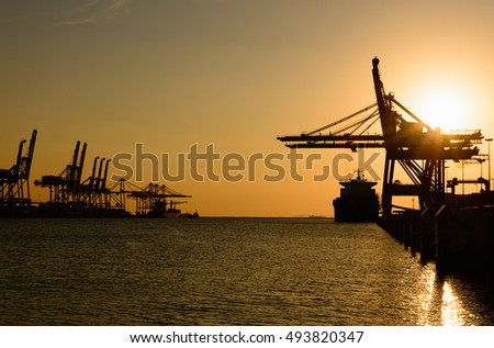Silhouette of container cargo and crane bridge