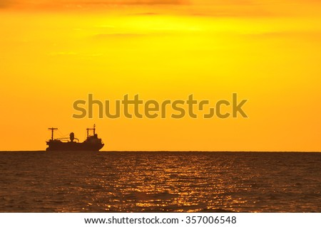 silhouette of container ship at the sea.