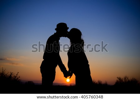 silhouette of couple at sunset, kiss