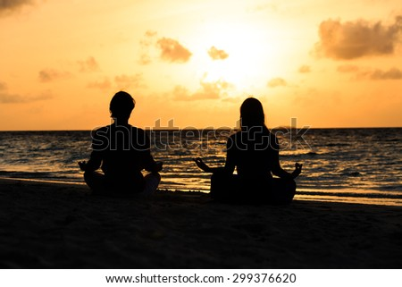 silhouette of couple doing yoga at sunset beach