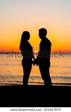 Silhouette of couple facing each other on the beach at sunrise. - stock photo