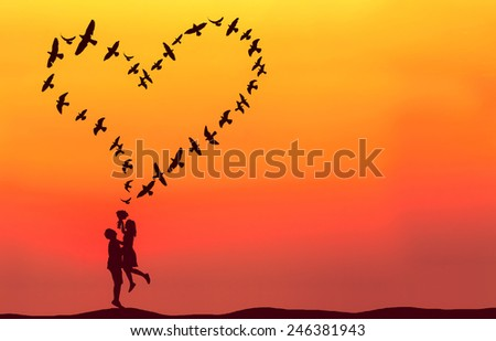Silhouette of couple in love with heart shaped made by flying birds.
