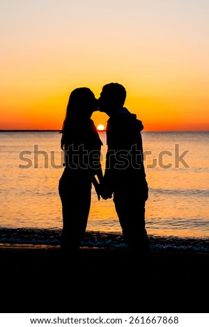 Silhouette of couple kissing each other on the beach at sunrise. - stock photo