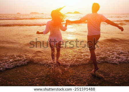 silhouette of couple on the beach, dream vacations - stock photo