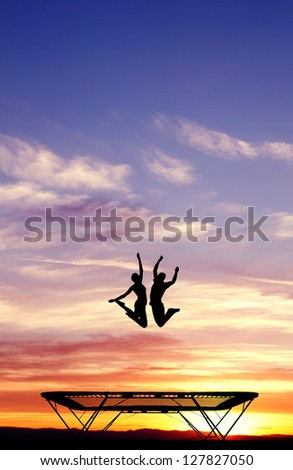 silhouette of couple on trampoline - stock photo