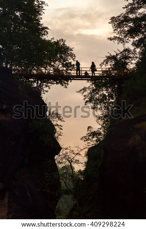 silhouette of couple on wooden bridge on a cliff of Aob Luang national park in norther thailand - stock photo