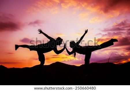 silhouette of couple posing, touching hands on mountain with beautiful sky background, summertime - stock photo