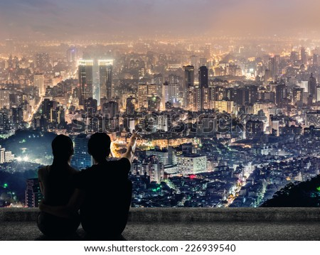 Silhouette of couple sit on ground point faraway on the roof above the city in the night. - stock photo