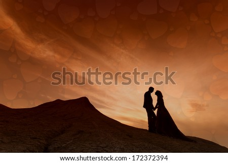 Silhouette of couple with red sky full of hearts