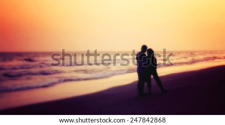 silhouette of couples hugging on the beach on the beach with sunrise in the sea for valentine's day, blurred - stock photo